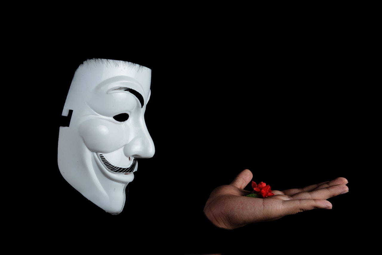 anonymous mask hand out red flower